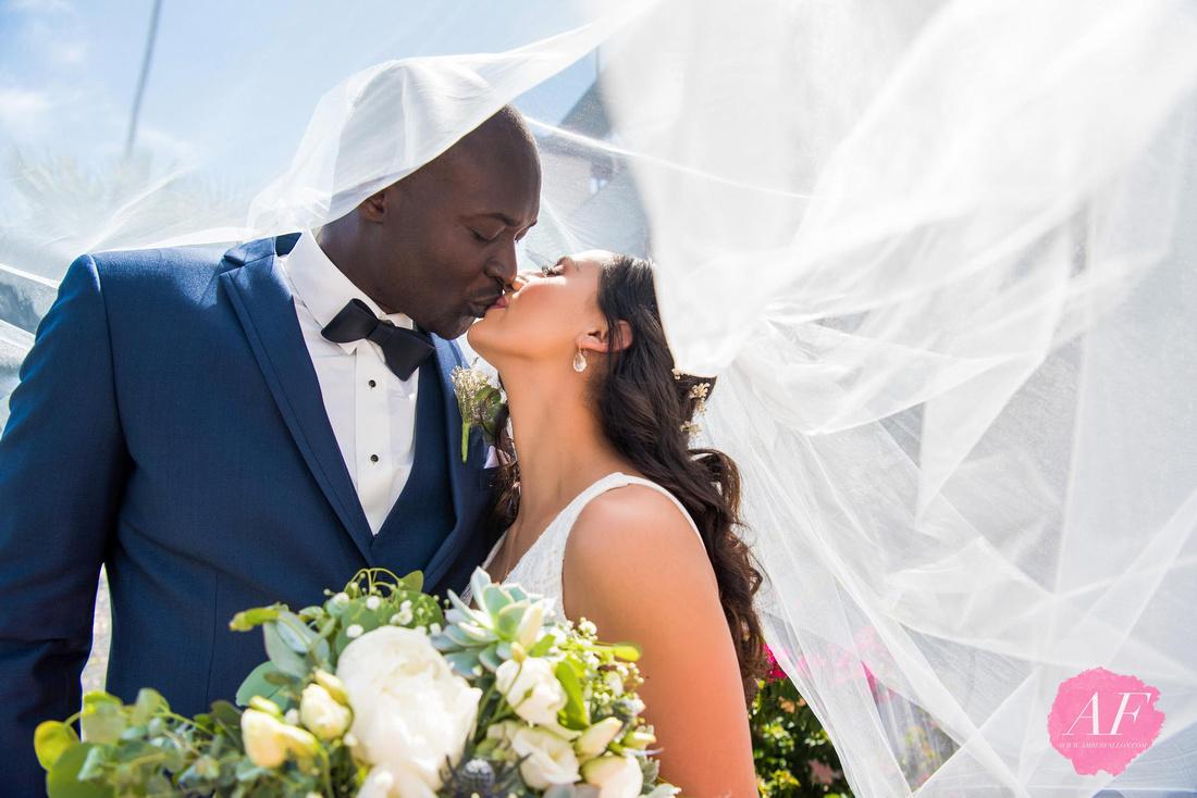 Wedding veil photo of multi-cultural bride and groom at beach during wedding day at Ole Hanson Beach Club in San Clemente, California