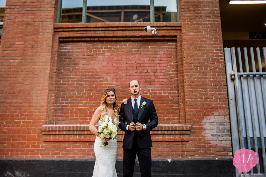 Modern couple in front of brick wall at Petco Park in downtown San Diego, California on their wedding day at the Ultimate Skybox reception venue.