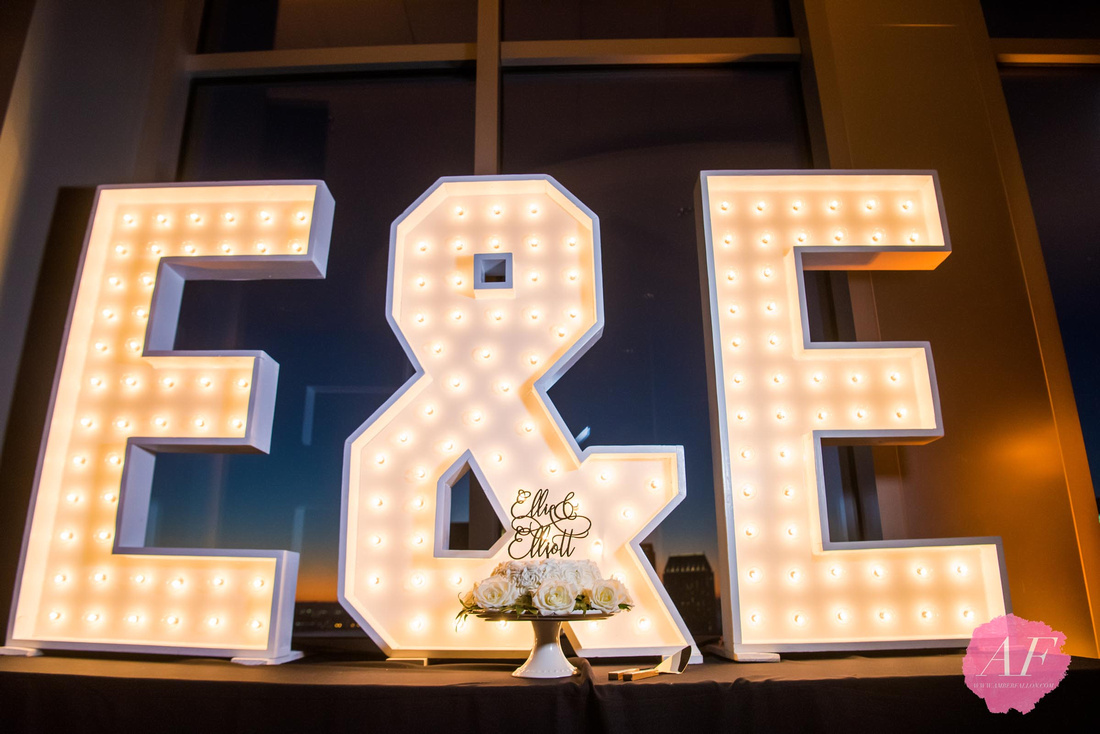 Creative and modern wedding cake and event lighting for bride and groom's reception in downtown san diego, california at the Ultimate Skybox reception venue.