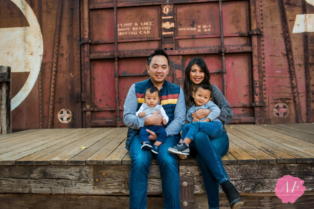 San Diego family photographer Amber Fallon Photo photographs young professional Chinese-American family photo session with two young toddlers sitting in front of red train caboose at a rustic, nature park named Old Poway Park in San Diego, California