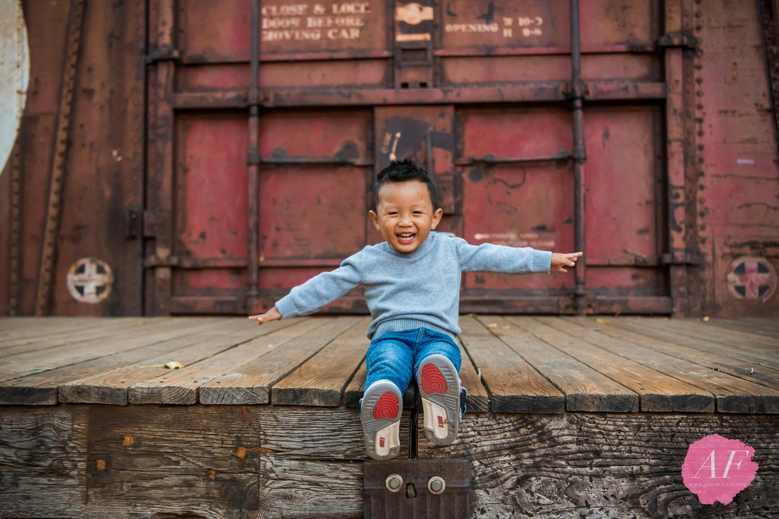 San Diego family photographer Amber Fallon Photo photographs young chinese american boy in front of red train caboose during a family photo session at a rustic, nature park named Old Poway Park in San Diego, California