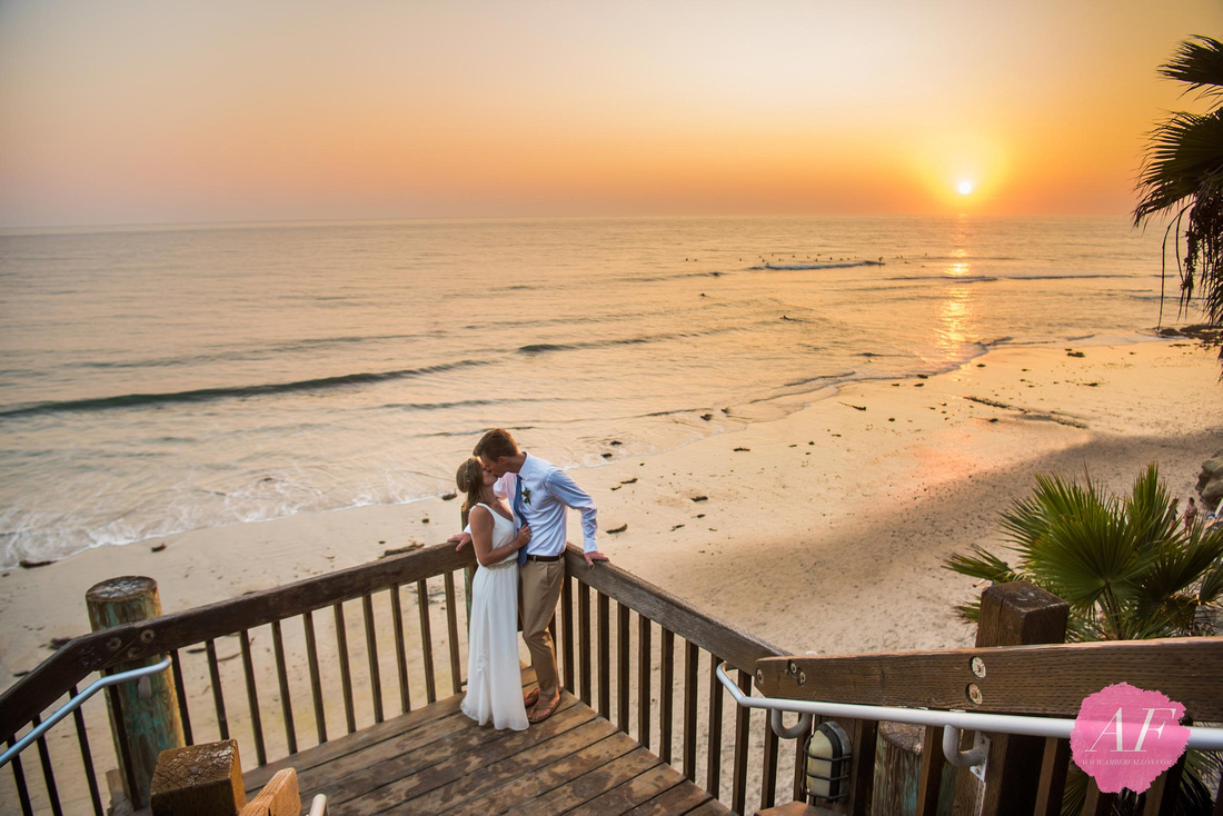 Surfer wedding couple pose for romantic sunset portraits after intimate beach elopement in Encinitas, California