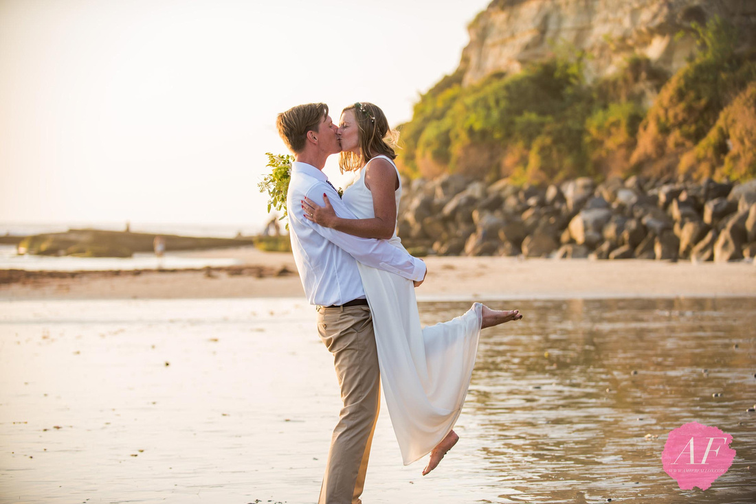 Surfer, vanlife wedding couple pose for romantic portraits during sunset after intimate beach elopement in Encinitas, California