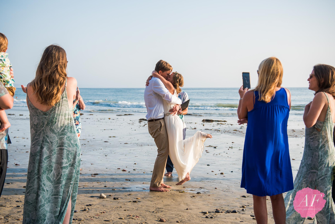 Surfer, vanlife wedding couple share first kiss as married husband and wife during sunset at intimate beach elopement in Encinitas, California