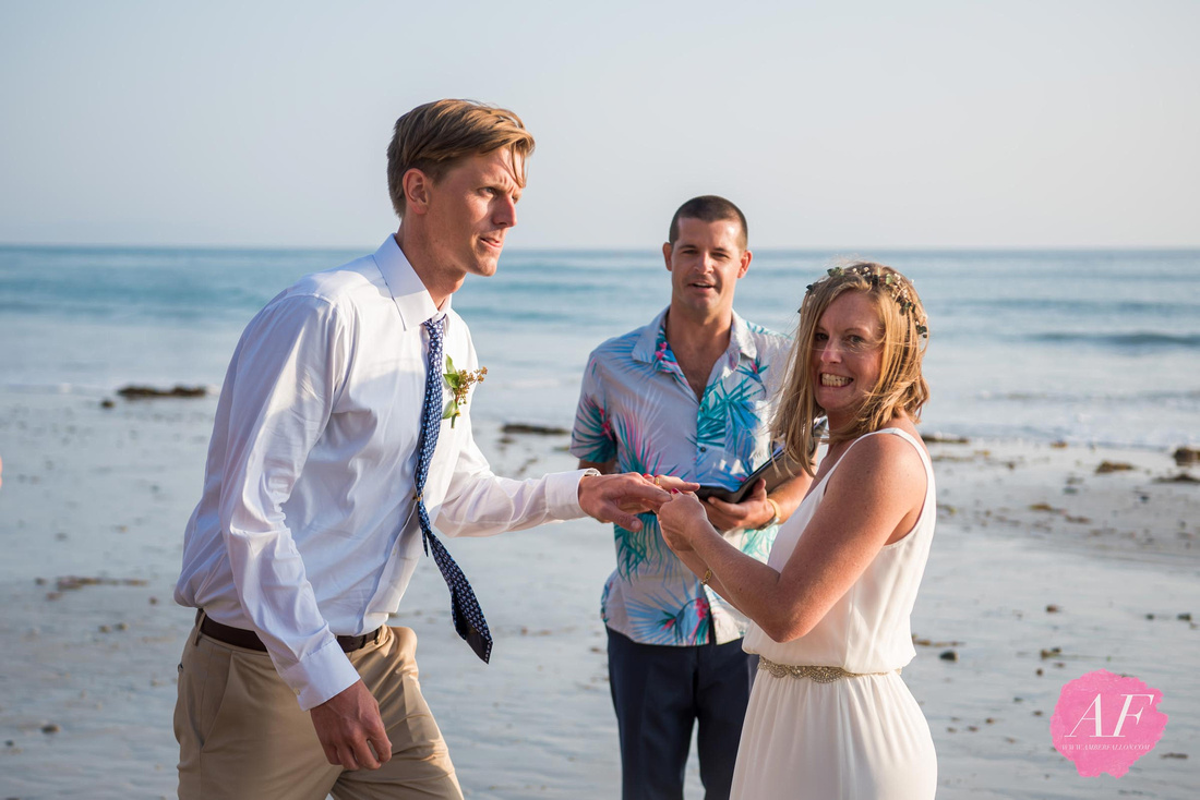 Surfer, vanlife wedding couple trade rings during sunset at intimate beach elopement in Encinitas, California